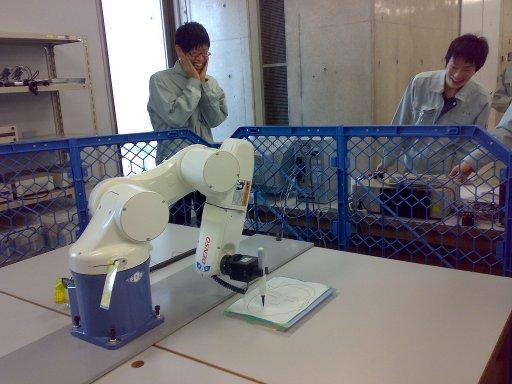 ロボットが似顔絵を書くことを心配そうに見つめる学生